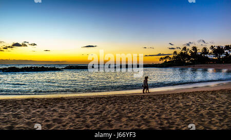 Couple walking at sunset along the beach of Honu Lagoon, the 2nd lagoon, and the Pacific Ocean with colorful sky - Stock Photo