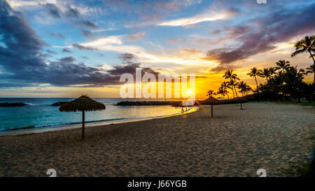Sunset over the beach of Honu Lagoon, the 2nd lagoon, and the Pacific Ocean with colorful sky at Ko Olina on the - Stock Photo