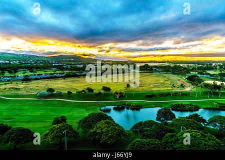 Sunrise over the horizon with sun peeking under dark morning clouds at the resort community of Ko Olina on the island - Stock Photo