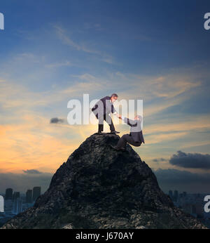 two of asian business man helping hand to climbing up to peak of rock mountain abstract of team work and partner - Stock Photo