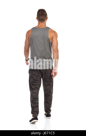 Fit man walking in tracksuit pants with camo, gray tank top and black sneakers. Rear view. Full length studio shot - Stock Photo