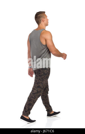 Young man walking in tracksuit pants with camo, gray tank top and black sneakers. Side rear view. Full length studio - Stock Photo