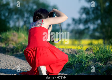 Woman in red dress with a camera taking  pictures - Stock Photo