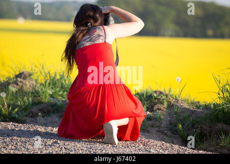 Female photographer taking summer pictures - Stock Photo