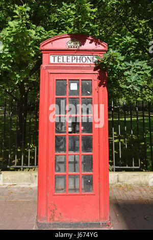 Old Red British Telephone Box on a sidewalk by Battersea Park. - Stock Photo
