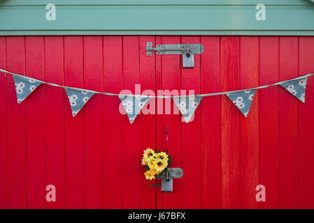 Bright yellow flowers and bunting on vivid red doors, beach hut ,Hove, Sussex - Stock Photo