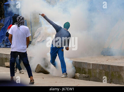India. 19th May, 2017. A protester returns a tear gas canister during clashes in Srinagar the summer capital of - Stock Photo