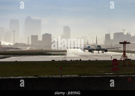 Two British Airways airplanes on runway at London City Airport - Stock Photo