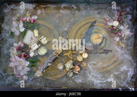 Original art still life: two pair of scissors grappled with handles and lie on a round brass plate among the flowers - Stock Photo