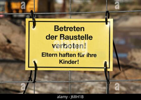 yellow warning sign at German construction site - Stock Photo