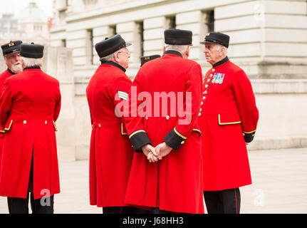 Group of ex-forces personnel known as the Chelsea Pensioners, standing in a small group talking to each other in - Stock Photo