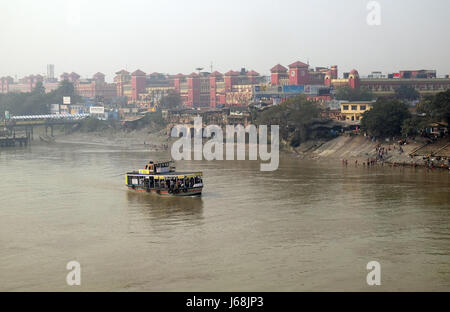 Ferry boat crosses the Hooghly River nearby the Howrah Bridge in Kolkata on February 10, 2016. To use the ferry - Stock Photo