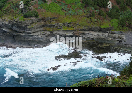 Overcast Stormy Waves Crashing On Rocks By Cliffs - Stock Photo
