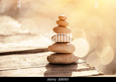 Spa stones still life on the beach, stack of pebbles on the boardwalk over sea in sunset light, peace and relaxation - Stock Photo