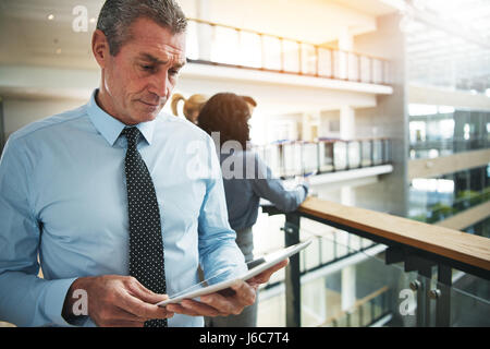 Mature business man standing and browsing tablet computer in office. - Stock Photo