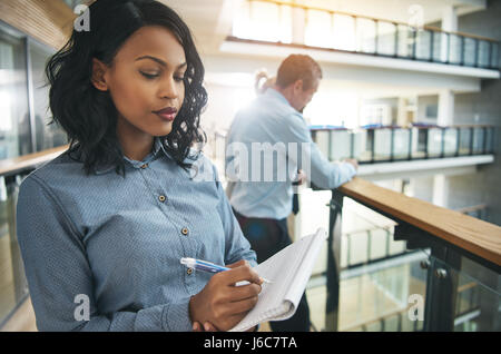 Pretty young African-American businesswoman writing in notepad and thinking in office. - Stock Photo