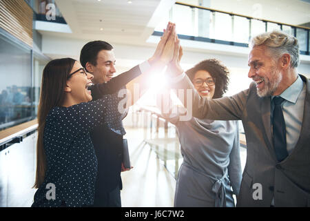 Smiling and laughing office working black and white men and women standing and giving high five to each other. - Stock Photo