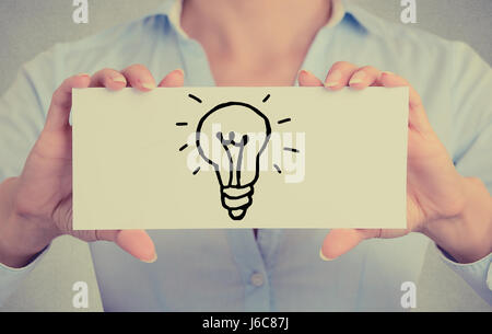 Closeup businesswoman hands holding white card sign with hand drawn illuminated light bulb isolated on grey wall - Stock Photo