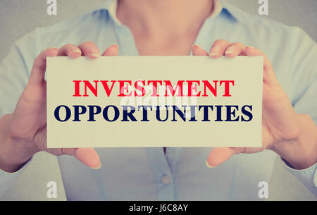 Businesswoman hands holding white card sign with Investment Opportunities text message isolated on grey wall office - Stock Photo