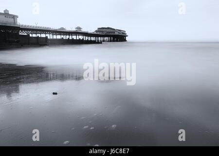 Low tide at Cromer Pier in black and white with a long exposure to smooth the waves and add an ethereal feel to - Stock Photo