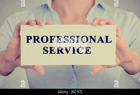 Closeup businesswoman hands holding Professional service sign card towards you, vintage retro filter effect toned - Stock Photo