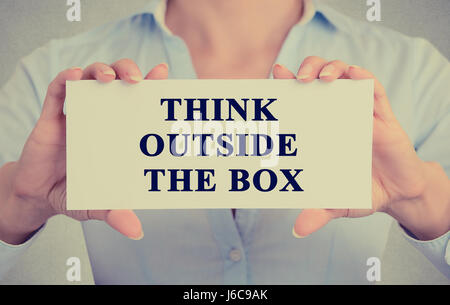 Closeup retro image businesswoman hands holding white sign or card with message think outside the box isolated on - Stock Photo