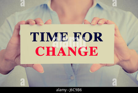 Businesswoman hands holding white card sign with time for change text message isolated on grey wall office background. - Stock Photo