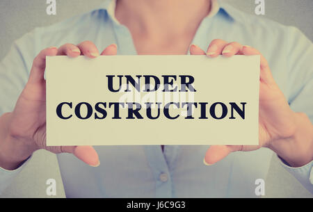 Closeup businesswoman hands holding white card sign with under construction text message isolated on grey wall office - Stock Photo