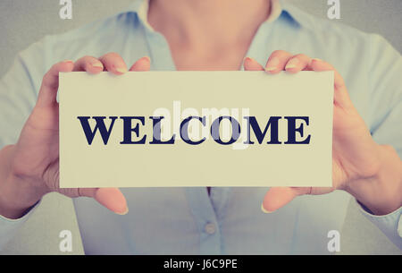 Closeup businesswoman hands holding white card sign with welcome text message isolated on grey wall office background. - Stock Photo