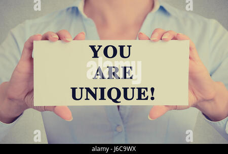 Closeup businesswoman hands holding white card sign with you are unique text message isolated on grey wall office - Stock Photo