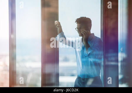 Happy businessman standing by window and talking on cell phone. Male executive inside office building and using - Stock Photo