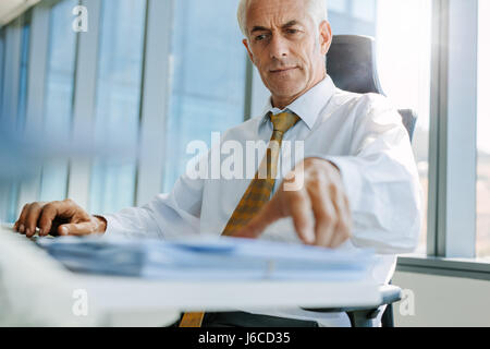 Shot of mature businessman sitting at his desk and working. Senior male entrepreneur in his office. - Stock Photo