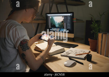 Photo of young woman designer sitting indoors at night play games by mobile phone. - Stock Photo