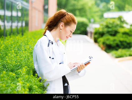 Portrait, young confident female doctor, healthcare professional reading patient chart isolated background outside - Stock Photo