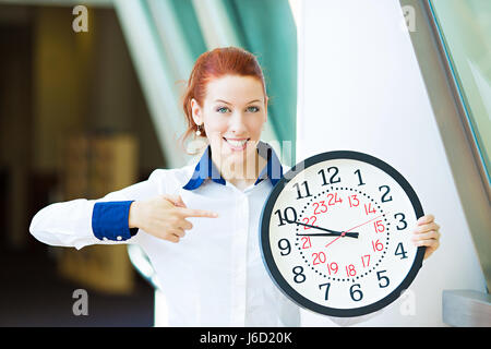 Closeup portrait smiling female, young businesswoman employee manager standing in corporate office hallway pointing - Stock Photo