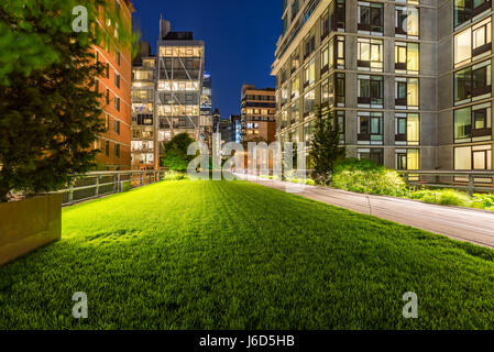 Highline promenade and lawn at twilight with city lights in the heart of Chelsea. Manhattan, New York City - Stock Photo