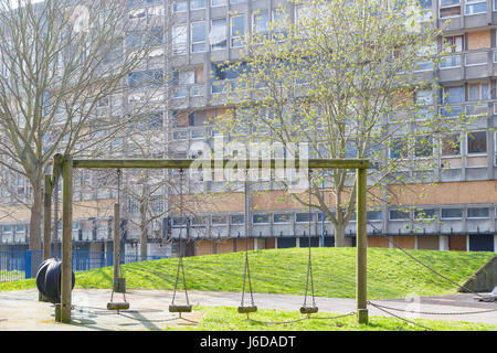 Old wooden playground and swings with a dilapidated council flat housing block, Robin Hood Gardens, in the background - Stock Photo