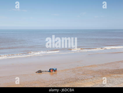 A fisherman's tractor and boat trailer waiting on Cromer beach, Norfolk, UK - Stock Photo