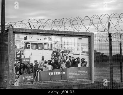 Monochrome photo of poster of last political prisoners to be freed from Robben Island near barbed wire ringed prison - Stock Photo
