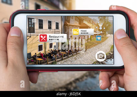 Augmented reality marketing concept. Hand holding smart phone use AR application to check relevant information about - Stock Photo