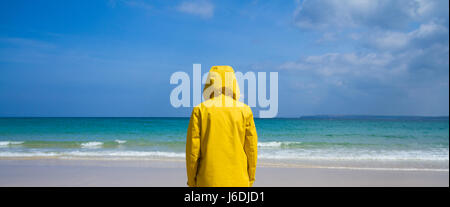 A single woman wearing a bright yellow, hooded jacket whilst standing on a deserted, sandy beach on a tropical paradise island.