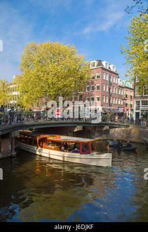 Boat passing under bridge of Prinsengracht canal, Amsterdam, Netherlands - Stock Photo