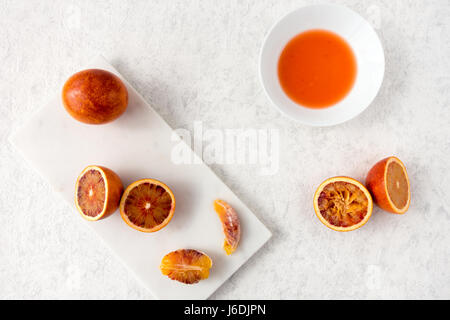 Whole, halved and squeezed blood oranges and fresh juice on white marble chopping board and white textured marbled - Stock Photo