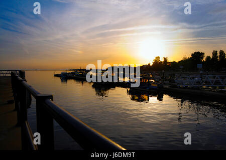 Olhao water front sun going down boats in front - Stock Photo