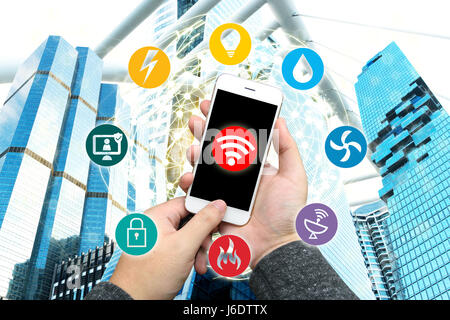 Smart Building and Internet of Things concept. Hand holding smartphone . Technology icons on office building and - Stock Photo