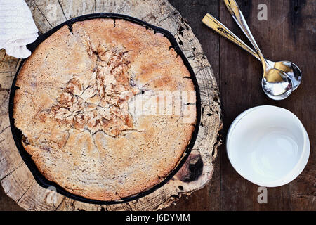 Above image of a blueberry and peach cobbler baked in a cast iron skillet over a rustic wood table top. Image shot - Stock Photo