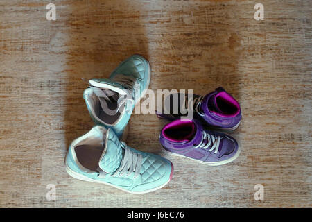Two pairs of sneakers. Adult and kids size. Mother and daughter. Blue and violet colors. - Stock Photo