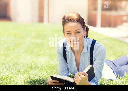 Happy student girl excited to get back to school university. Beautiful woman reading book, laying down on green - Stock Photo