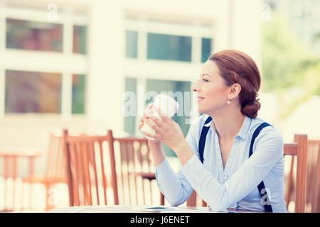 Side profile portrait woman drinking coffee in sun sitting outdoor in sunshine light enjoying her morning tea. Smiling - Stock Photo