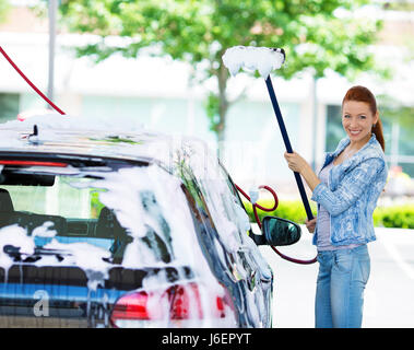 Picture, portrait young, smiling, happy, attractive woman washing automobile at manual car washing self service - Stock Photo